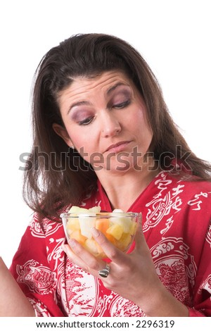 Pretty brunette looking a bit surprised at the contents of her fruitbowl - stock photo