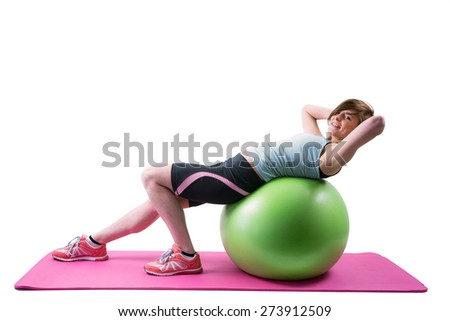 Pretty brunette looking at camera and exercising on fitness ball on white background - stock photo