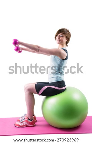 Pretty brunette looking at camera and exercising with dumbbells on fitness ball on white background - stock photo