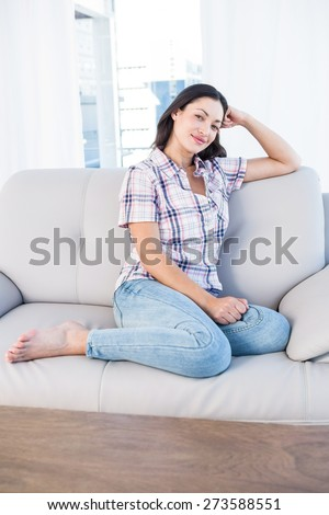 Pretty brunette looking at camera and sitting on couch in the living-room