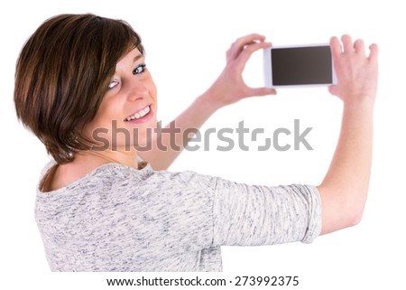 Pretty brunette looking at camera and taking a picture with her smartphone on white background - stock photo