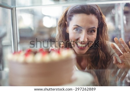 Pretty brunette looking at chocolate cake through the glass in the bakery store - stock photo