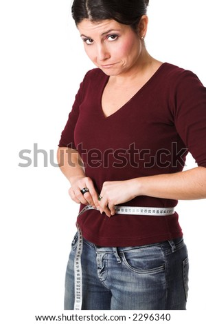 pretty brunette looking very disappointed while holding a measuring tape around her waist - stock photo