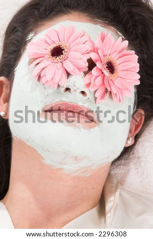 Pretty brunette lying on a towel with a claymask and flowers on her eyes - stock photo