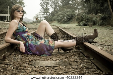 Pretty brunette on railway tracks