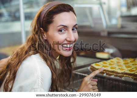 Pretty brunette pointing at pastries through the glass in the bakery store - stock photo