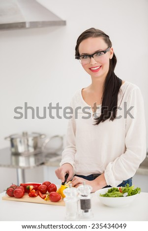 Pretty brunette preparing a healthy salad at home in the kitchen