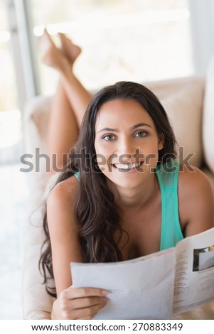 Pretty brunette reading magazine on the couch at home in the living room - stock photo