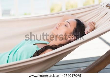 Pretty brunette relaxing on a hammock in patio - stock photo