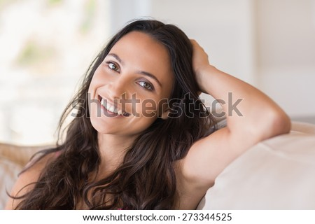 Pretty brunette relaxing on the couch at home in the living room - stock photo