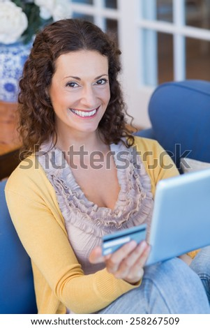 Pretty brunette relaxing on the couch with tablet in the living room - stock photo