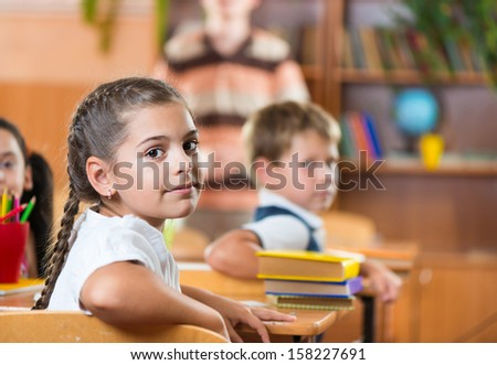 Pretty brunette schoolgirl during lesson at school - stock photo