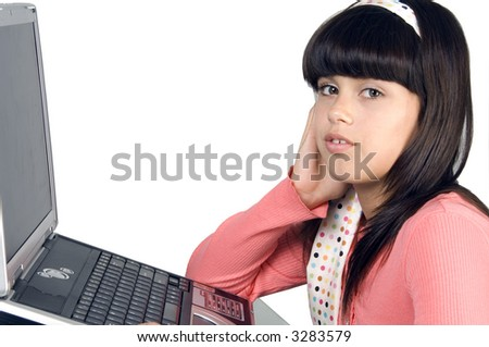 Pretty brunette schoolgirl in pink looks at you, notebook computer in front of her, isolated on white - stock photo