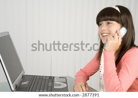 Pretty brunette schoolgirl in pink talking on cell phone, with bright smile, sitting by notebook computer and blinds - stock photo
