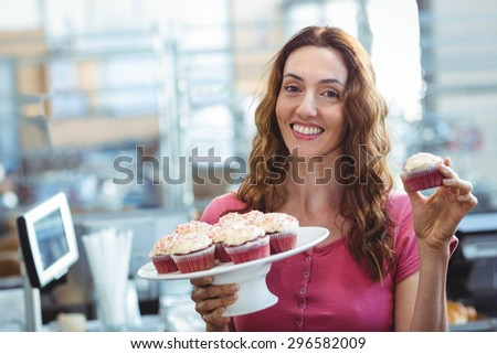 Pretty brunette showing cupcake at the bakery