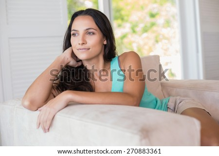 Pretty brunette sitting on the armchair at home in the living room