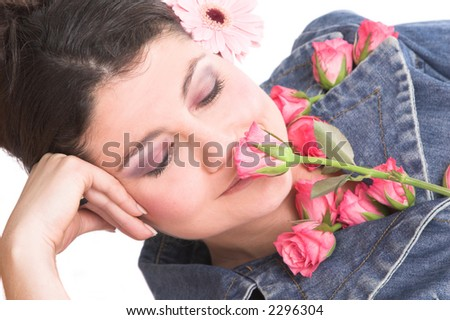 Pretty brunette smelling a pink rose while lying in relaxed pose - stock photo