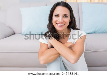 Pretty brunette smiling at camera at home in the living room - stock photo