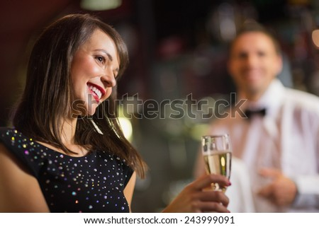 Pretty brunette smiling with champagne in a bar