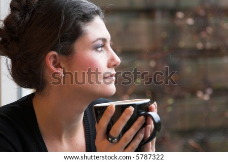 Pretty brunette staring out of the window and enjoying a cup of tea