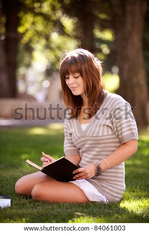 Pretty brunette student writing in a journal on a university campus - stock photo