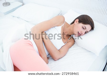Pretty brunette suffering from stomach pain at home in the bedroom - stock photo