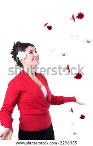 Pretty brunette surrounding by falling flowers with a happy smile on her face - stock photo