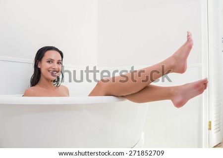 Pretty brunette taking a bath in a bathroom - stock photo