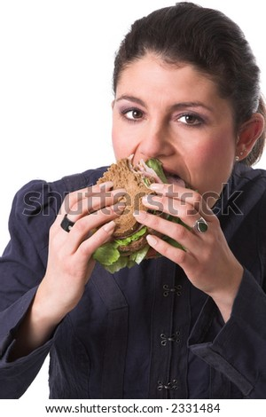 Pretty brunette taking a big bite of her healthy sandwich - stock photo