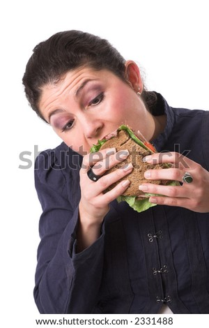 Pretty brunette taking a big bite out of a sandwich looking at her sandwich cross-eyed
