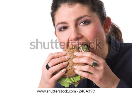 Pretty brunette taking a big bite out of her healthy sandwich - stock photo