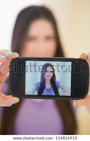Pretty brunette taking a photo of herself with her mobile phone in a bedroom - stock photo