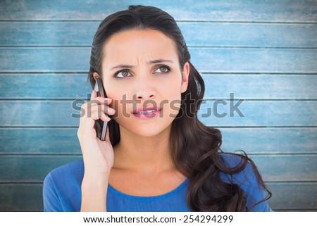 Pretty brunette talking on the phone against wooden planks - stock photo