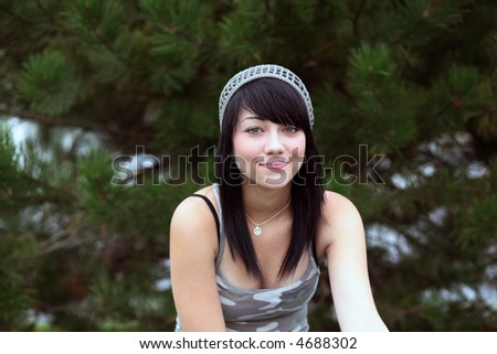 pretty brunette teen girl smiling in front of evergreen