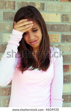 pretty brunette teen girl with a look of distress - stock photo
