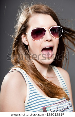 Pretty brunette teenage girl with sunglasses. Studio shot.