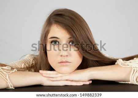 Pretty brunette teenager girl, with long brown hair, wearing an off white dress, looking  at the camera seriously, arms resting on a table - stock photo