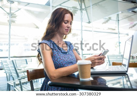 Pretty brunette using her laptop in a coffee shop - stock photo