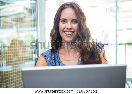 Pretty brunette using her laptop in a coffee shop