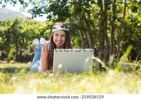 Pretty brunette using laptop in park on a summers day - stock photo