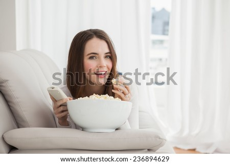 Pretty brunette watching tv with popcorn at home in the living room