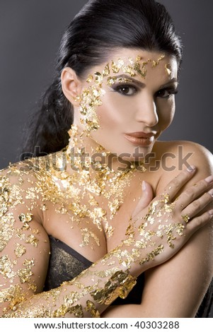 pretty brunette wearing gold outfit and matching makeup