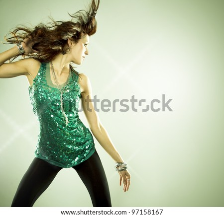 pretty brunette wearing green outfit on light background - stock photo