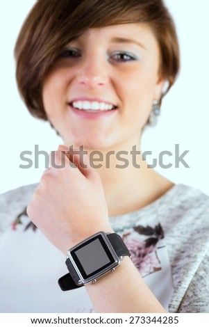 Pretty brunette wearing her smartwatch on white background - stock photo