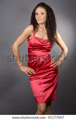 pretty brunette wearing red dress on grey background