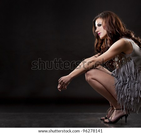 pretty brunette wearing silver party dress on black background