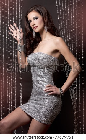 pretty brunette wearing silver party dress on black background - stock photo