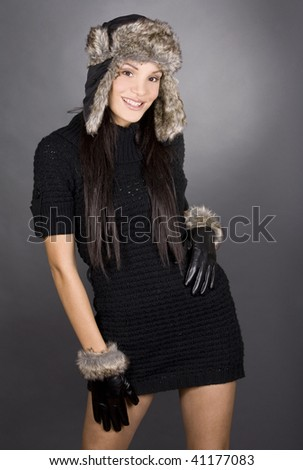 pretty brunette wearing winter outfit on grey background