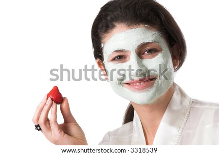Pretty brunette with a facial beauty mask on her face and a fresh strawberry in her hand