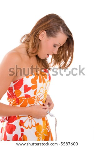 Pretty brunette with a measuring tape around her waist looking surprised - stock photo